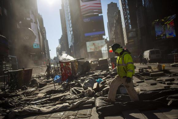 A worker walks while repairing the road at Times Square in New York  (REUTERS/Eric Thayer)