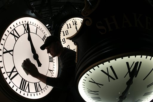 Dave LeMote wipes down a post clock at Electric Time Company, Inc. in Medfield, Mass. (AP Photo/Elise Amendola)