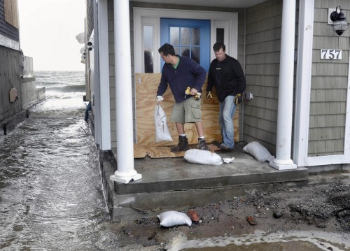 Ken Esposito, left, helps his neighbor Rob Hoxie sandbag his beachfront home before high tide in Milford, Conn.( AP Photo/Jessica Hill, File)