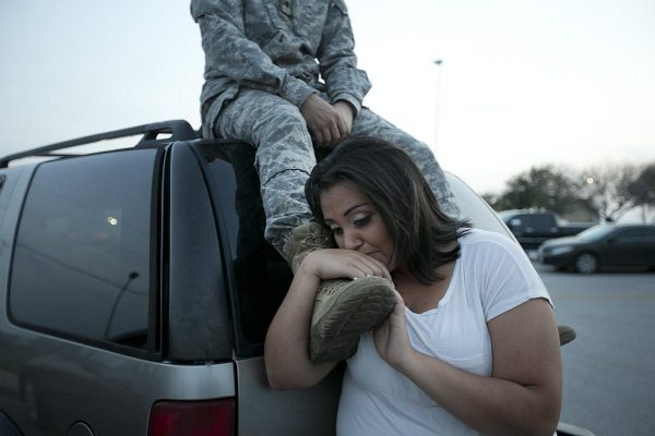 Lucy Hamlin leans on her husband's foot, Specialist Timothy Hamlin, as they wait to be allowed back onto Fort Hood, Texas, where they reside.  (AP Photo/Austin American-Statesman, Deborah Cannon)
