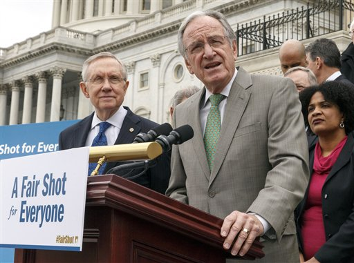 Senate Health, Education, Labor and Pensions Committee Chairman Sen. Tom Harkin, D-Iowa, right, accompanied by Senate Majority Leader Harry Reid of Nev., left, and others.  (AP Photo/J. Scott Applewhite, File)