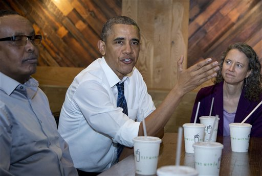 President Barack Obama flanked by Abdullahi Mohamed, left, and Meredith Upchurch speaks to reporters at a restaurant in Washington, Friday.  The president and Vice President Joe Biden met with construction workers involved in a recent infrastructure project.   (AP Photo/Manuel Balce Ceneta)