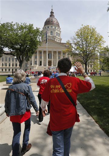 Public education supporters march to the Kansas Statehouse for a rally in Topeka, Kan. (AP Photo/Orlin Wagner)
