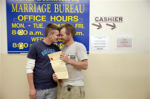 William Roletter, left, and Paul Rowe, press close to one another after they had their photo made with their newly acquired marriage certificate, Wednesday at City Hall in Philadelphia. . (AP Photo/Matt Rourke)
