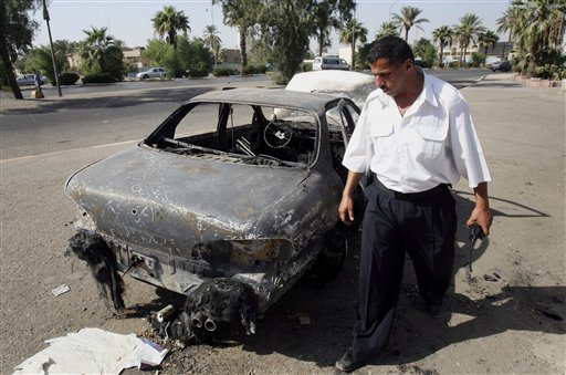 Iraqi traffic policeman inspecting a car destroyed by a Blackwater security detail.  (AP Photo/Khalid Mohammed)
