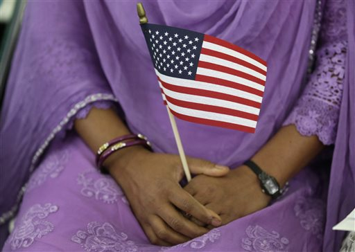 A new U.S. citizen holds an American flag at a naturalization ceremony at the Benjamin Harrison Presidential Site in Indianapolis, Thursday.  (AP Photo/Michael Conroy)