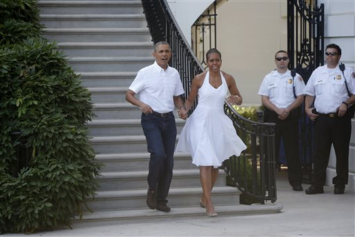 President Barack Obama and first lady Michelle Obama walk from the South Portico to greet military families as they host an Independence Day celebration on the South Lawn at the White House in Washington.  (AP Photo/Charles Dharapak)