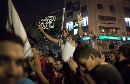 Palestinians dance while flying a Palestinian Islamic Jihad Movement flag   (AP Photo/Nasser Nasser)