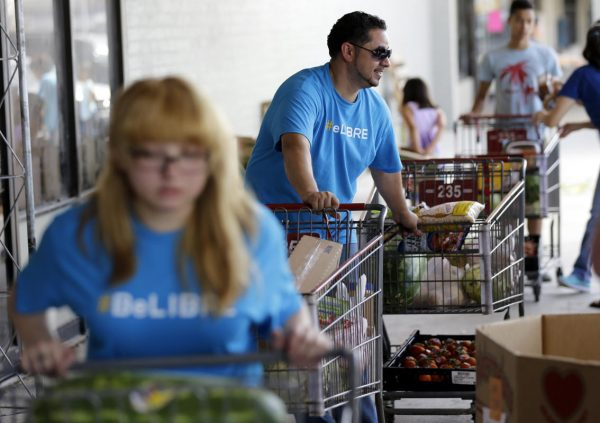 Pastor Marcus Burgos, center, and other volunteers load groceries at a food bank at the Abundant Life Church in San Antonio. The food bank is cosponsored by the Libre Initiative, partly funded by conservative billionaires Charles and David Koch (AP Photo/Eric Gay)