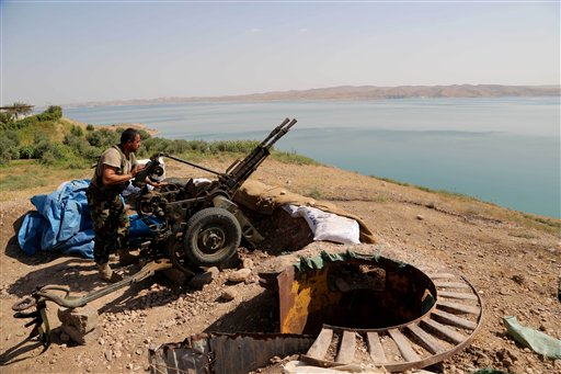 A Kurdish peshmerga fighter prepares his weapon at his combat position near the Mosul Dam at the town of Chamibarakat outside Mosul, Iraq  (AP Photo/Khalid Mohammed)