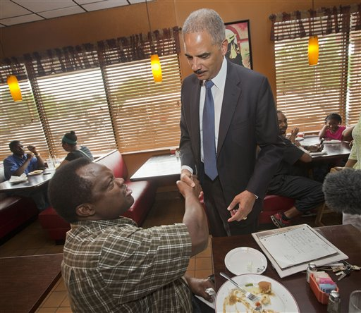 Attorney General Eric Holder shakes hands with a patron at Drake's Place Restaurant, before his meeting with local community leaders, Wednesday. (AP Photo/Pablo Martinez Monsivais, Pool)
