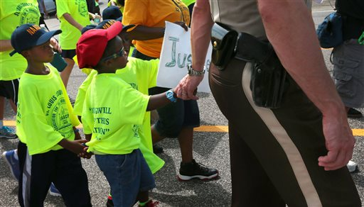 St. Louis County Police Sgt. Colby Dolly joins hands with five-year-old Zion King Frenchie during a march with members of the St. Louis chapters of the NAACP and the National Urban League on West Florissant Avenue in Ferguson, Mo., on Saturday (AP Photo/St. Louis Post-Dispatch, Robert Cohen)