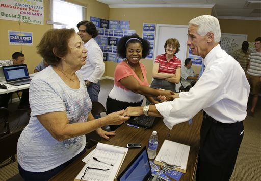 Former Florida Gov. Charlie Crist, right, thanks campaign volunteers for their support during a visit to a calling bank Monday,  (AP Photo/John Raoux)