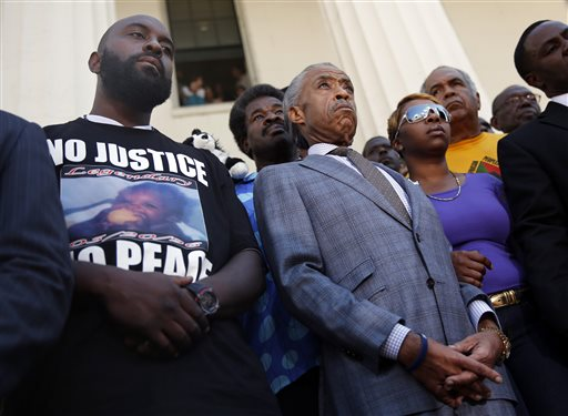 Rev. Al Sharpton, center, stands with the parents of Michael Brown (AP Photo/Jeff Roberson)