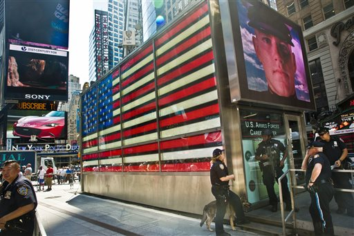 Officers with the NYPD anti-terrorism unit guard a military recruiting station in Times Square. (AP Photo/Bebeto Matthews)
